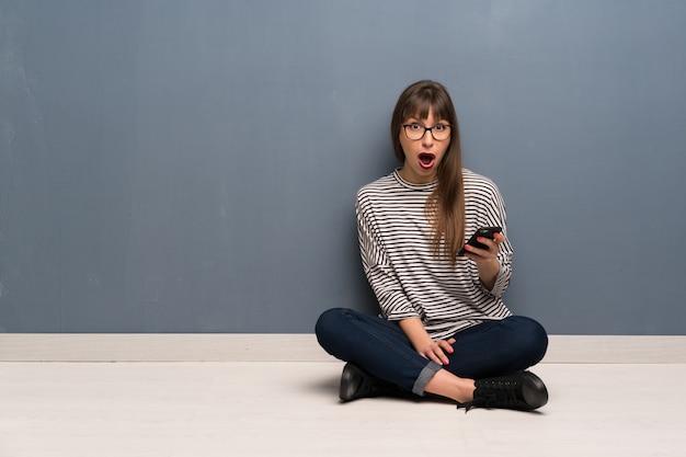 Frau mit brille auf dem boden sitzen überrascht und eine nachricht senden