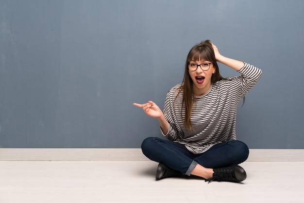 Frau mit brille auf dem boden sitzen überrascht und finger auf die seite zeigen