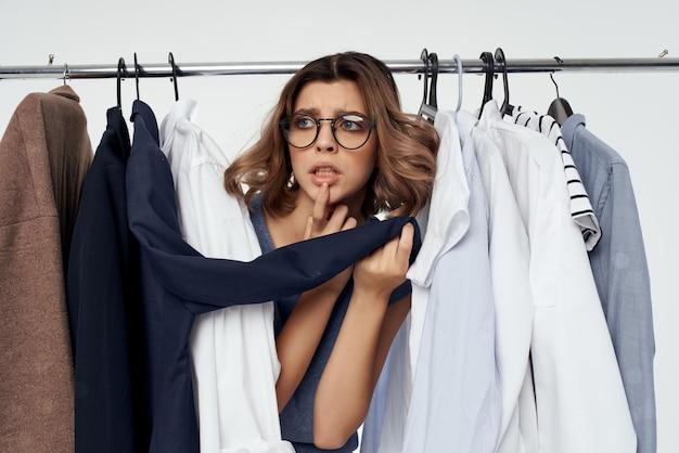 Frau mit brille bekleidungsgeschäft käufer verkauf hellen hintergrund. foto in hoher qualität