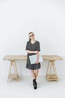 Frau mit brille, die in die kamera neben dem tisch schaut und einen laptop hält