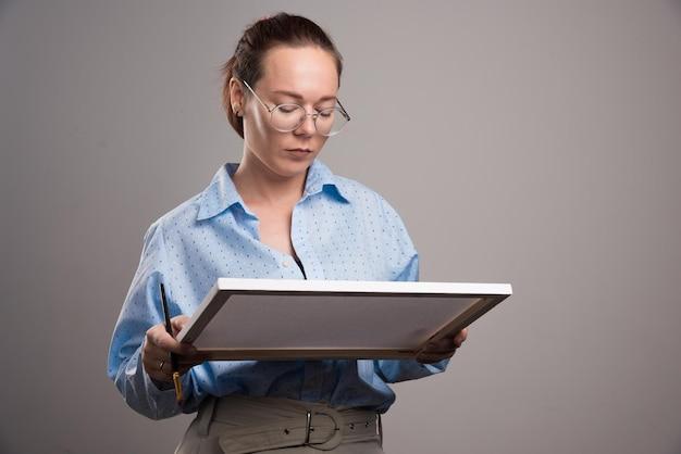 Frau mit brille, die leinwand und pinsel auf grau hält. foto in hoher qualität