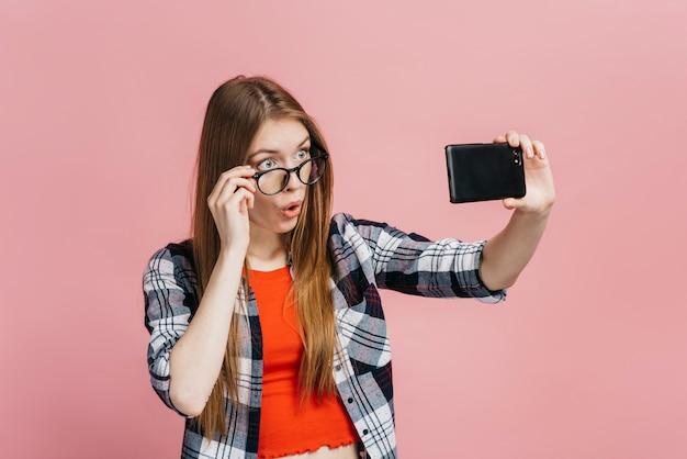 Frau mit brille ein selfie nehmen