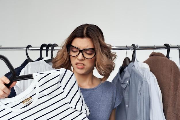 Frau mit brille in der nähe von kleidung shopaholic isolierten hintergrund. foto in hoher qualität