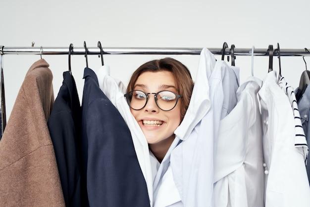Frau mit brille in der nähe von kleidung shopaholic isolierten hintergrund