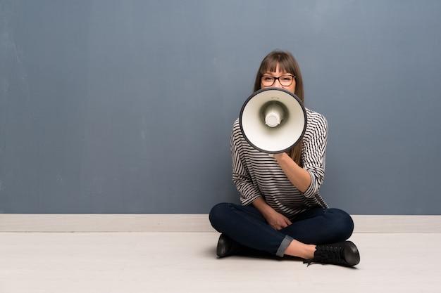 Frau mit brille sitzt auf dem boden und schreit durch ein megaphon