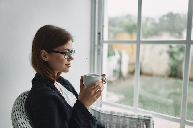 Frau mit brille sitzt zu hause am fenster mit einer tasse kaffee