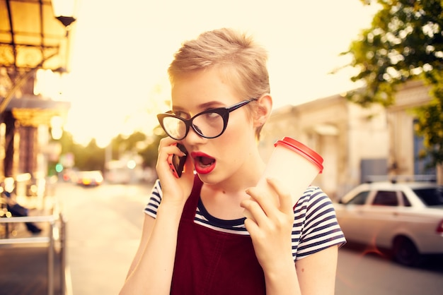 Frau mit brille telefoniert auf der straße eine tasse kaffee