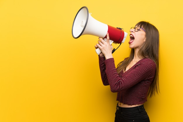 Frau mit brille über gelbe wand schreien durch ein megaphon