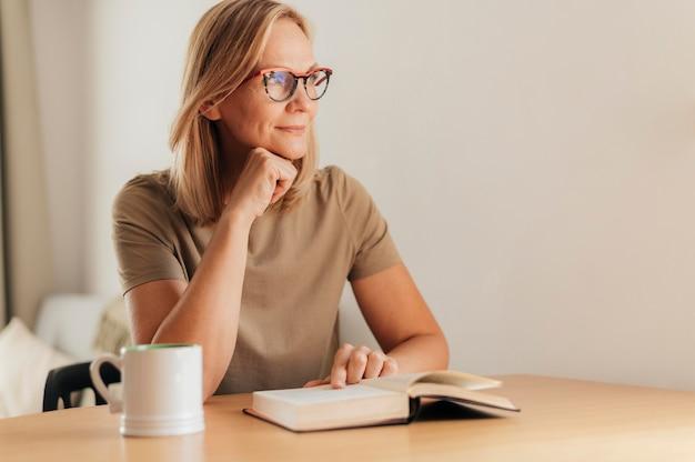 Frau mit brille zu hause beim lesen während der quarantäne