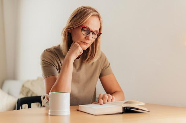 Frau mit brille zu hause, die buch während der quarantäne liest