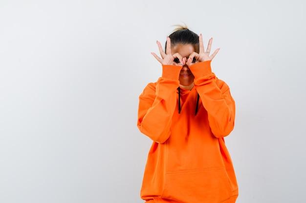 Frau mit brillengeste in orangefarbenem hoodie und neugierigem blick