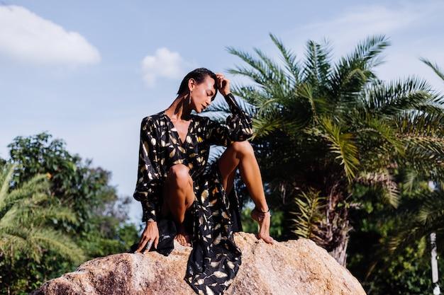 Frau mit bronze make-up im schwarzgoldenen kleid sitzt auf stein