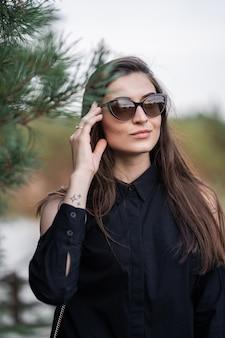 Frau mit brünetten haaren in dunkler kleidung und sonnenbrille. mode straßenfotografie. model posiert auf naturhintergrund. sonnenbrillenladen