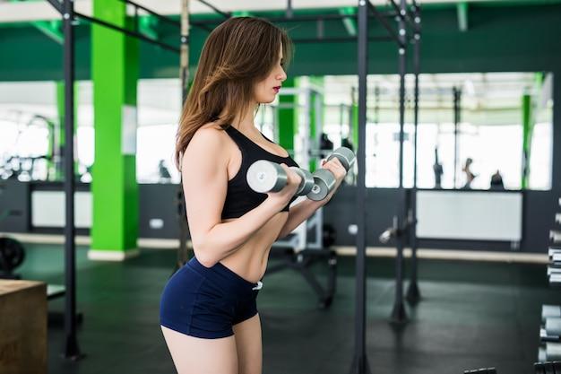 Frau mit brünetten haaren macht übungen im sportclub in schwarzer sportbekleidung
