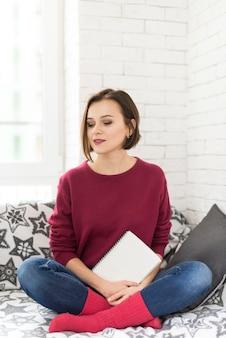 Frau mit buch in der hand auf dem sofa warten