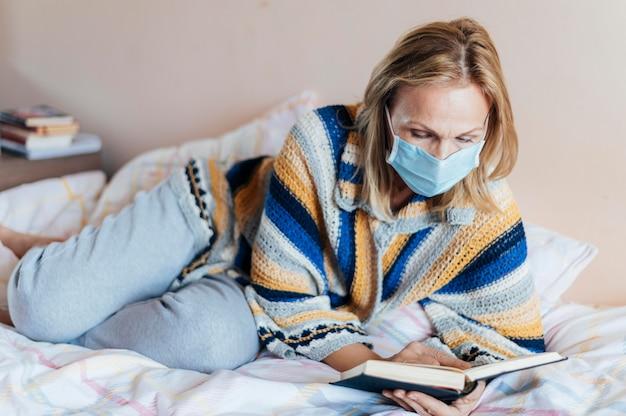 Frau mit buch und medizinischer maske in quarantäne zu hause