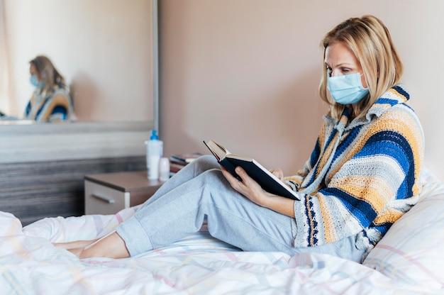 Frau mit buch und medizinischer maske in quarantäne