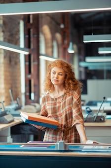 Frau mit büchern. lockige schöne frau, die ein schönes kleid trägt und bücher im verlagsbüro hält holding
