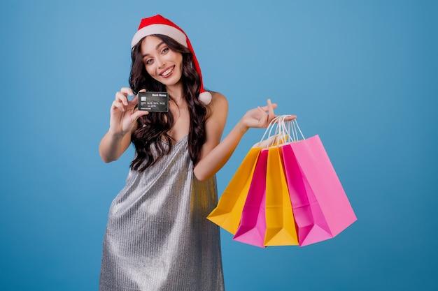 Frau mit bunten einkaufstaschen und der kreditkarte, die sankt-hut trägt