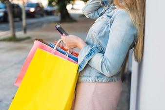 Frau mit bunten Einkaufstüten mit Smartphone