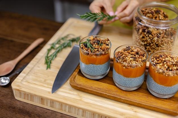 Frau mit bunten gesunden süßen wüsten-chia-puddings aus mandelmilch, blauem spirulina-extrakt, chiasamen, pappaya-mango-marmelade und hausgemachtem müsli. auf holztisch in der küche zu hause.