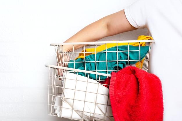 Frau mit bunten kleidern im wäschekorb