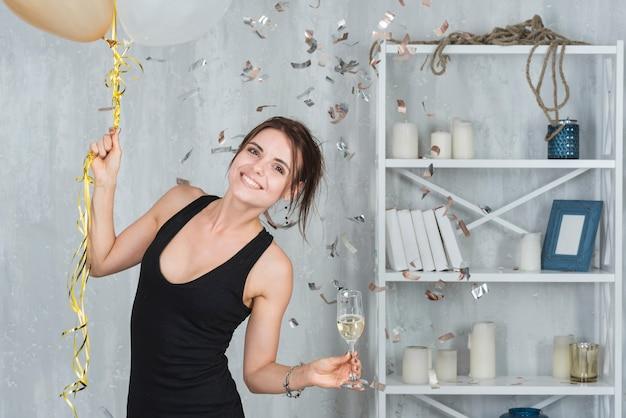 Frau mit champagner und luftballons