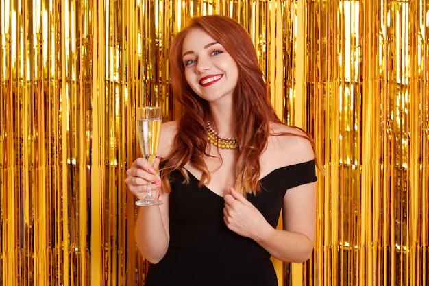 Frau mit charmantem lächeln feiert neujahr, hält glas wein, trägt elegantes schwarzes kleid, posiert gegen gelbe wand mit goldenem lametta.