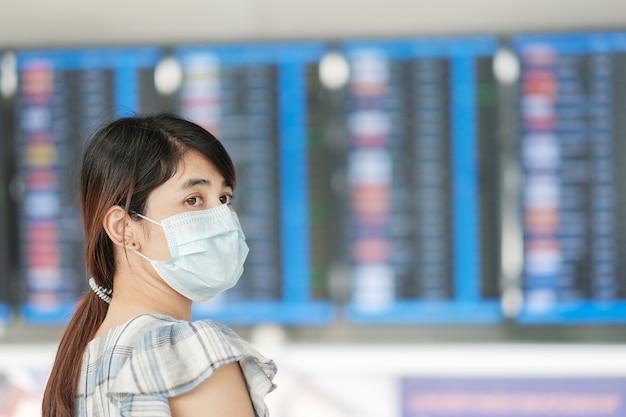 Frau mit chirurgischer gesichtsmaske am flughafen
