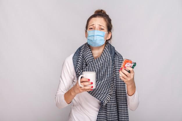 Frau mit chirurgischer medizinischer maske, weinen, weil sie krank war. holdingschale mit tee, vielen pillen und antibiotika. indoor, studioaufnahme, auf grauem hintergrund isoliert