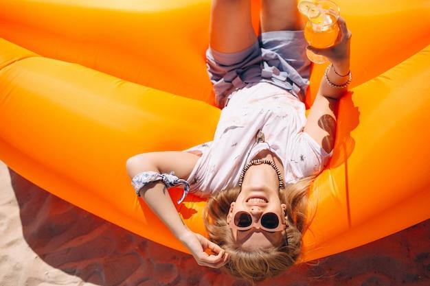 Frau mit coctail liegend auf einer poolmatratze am strand