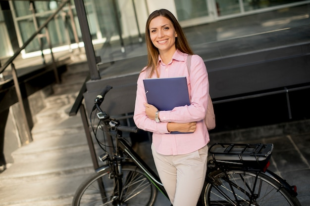 Frau mit dateien in den händen, die vor elektrischem fahrrad im freien stehen