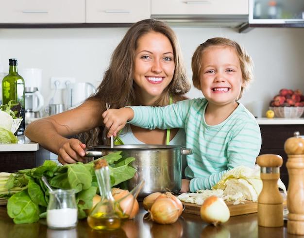 Frau mit dem baby, das an der küche kocht