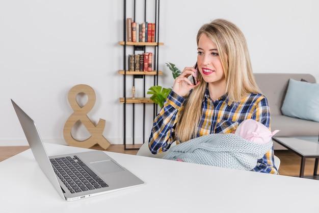 Frau mit dem baby, das über smartphone spricht