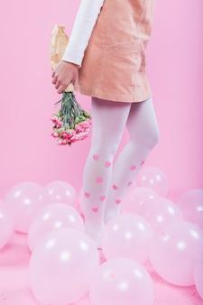 Frau mit dem Blumenblumenstrauß, der auf Boden mit Ballonen steht