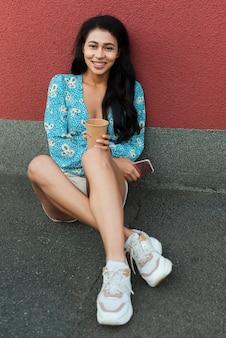 Frau mit dem blumenhemd, das ihr telefon sitzt und hält