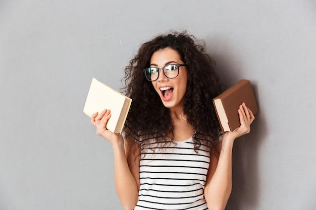Frau mit dem braunen gelockten haar, das student in der universität aufwirft mit interessanten büchern in den händen ist, welche die bildung genießen, die über grauer wand lokalisiert wird