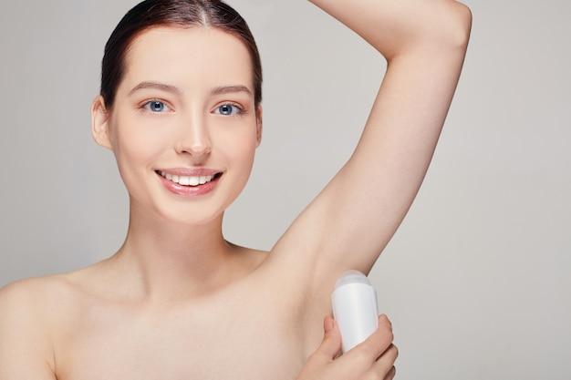 Frau mit dem braunen haar mit der sauberen frischen haut, die auf grau aufwirft