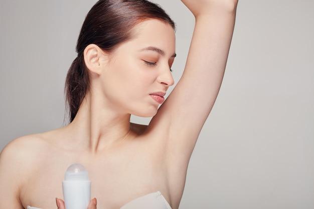 Frau mit dem braunen haar mit der sauberen frischen haut, die auf grau mit desodorierendem mittel in ihrer hand aufwirft
