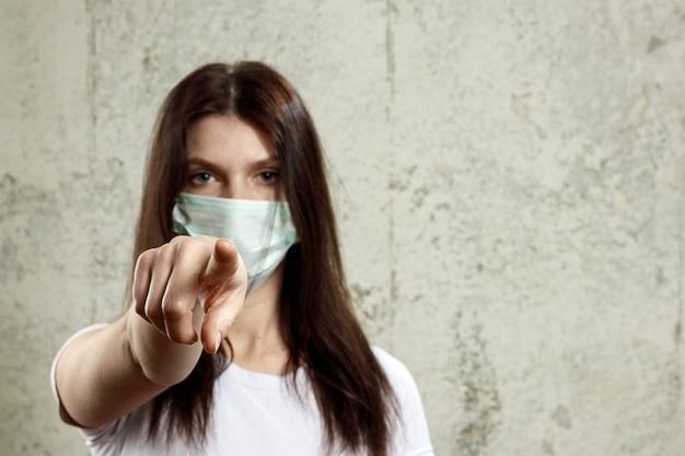 Frau mit dem braunen haar und einer medizinischen maske für schutzgewinngrippe