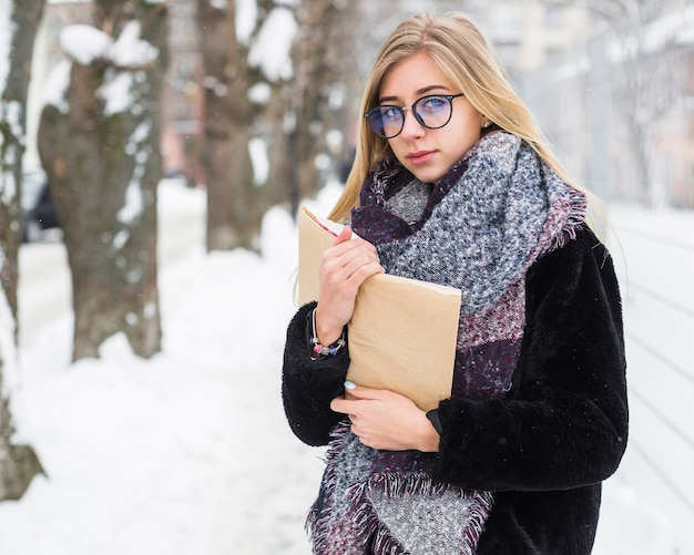 Frau mit dem buch, das kamera auf winterstraße betrachtet