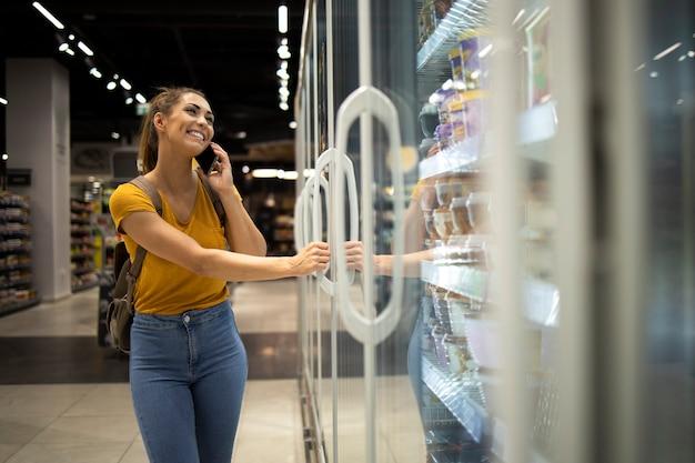 Frau mit dem einkaufswagen, der kühlschrank öffnet, um lebensmittel im lebensmittelgeschäft beim telefonieren zu nehmen