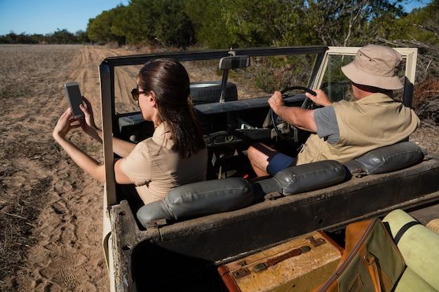 Frau mit dem fotografierenden mann beim reisen in fahrzeug