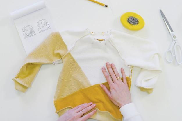 Frau mit dem freiberufler oder modedesigner oder schneider des blonden haares, die an design oder entwurf mit bunten geweben in der werkstatt arbeiten