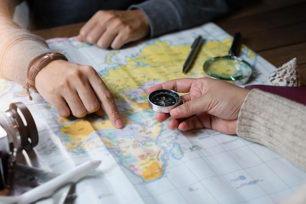 Frau mit dem freund, der für urlaubsreise mit zubehör des reisenden plant