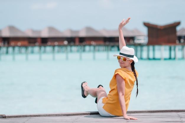 Frau mit dem gelben hut, der am swimmingpool im exotischen erholungsort sich entspannt