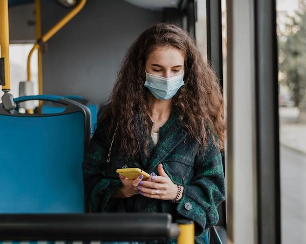 Frau mit dem gelockten haar, das medizinische maskenvoransicht trägt