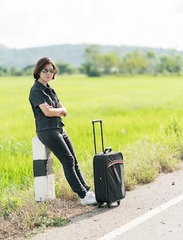 Frau mit dem gepäck, das entlang einer straße per anhalter fährt
