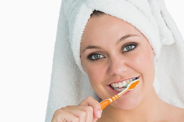 Frau mit dem haartuch, das ihre zähne wäscht
