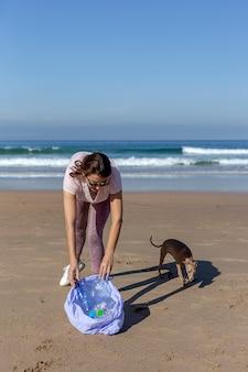 Frau mit dem hund, der abfall und plastik säubern den strand aufhebt